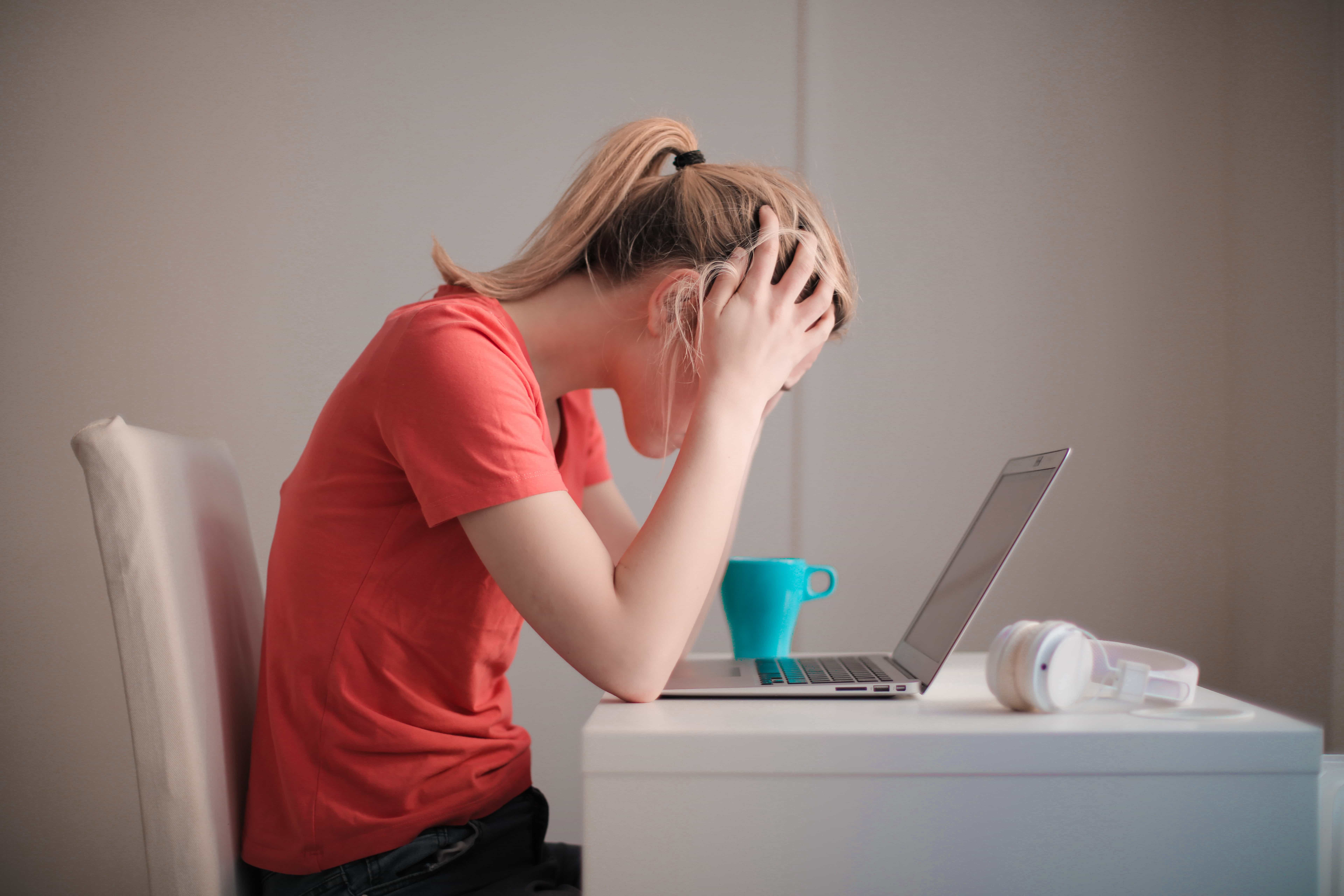 This is an image of a stressed out person sitting at their laptop with their head in their hands