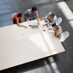 This is an image of four people sitting around a boardroom table having a meeting