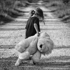This is an image of a girl carrying a large teddy bear down the street