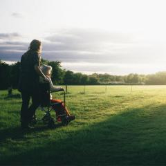 Person pushing an older woman in a wheelchair in a field at sunrise