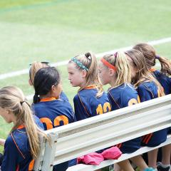 young girls in sports uniforms on bench looking at sports field