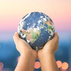 This is an image of someone holding a model of a globe in their hands
