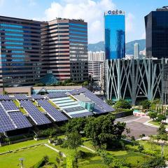 modern cityscape with lots of green area and a building covered in solar panels.
