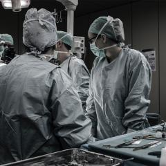Surgery in an operating theatre with doctors crowded around patient.