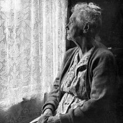 Elderly woman at window, photo by Chalmers Butterfield via Wikimeda Commons