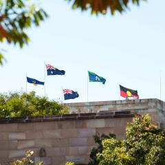 several flags on the roof of the Forgan Smith building at UQ