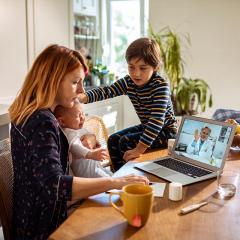 mother working on a laptop while holding baby and looking after child.