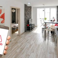 holiday home with a hand holding mobile phone with Airbnb app open.