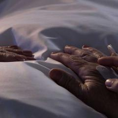 elderly woman's hands on resting on bed sheet