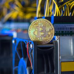 A gold bitcoin sitting on computing equipment used to 'mine' it