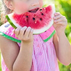 little girl eating a watermelon.