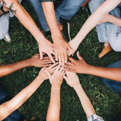 This is an image of a group of people touching hands in a circle
