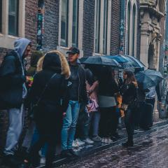 people waiting in line in the rain