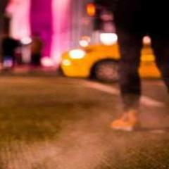 street at night with young person in yellow sneakers walking away